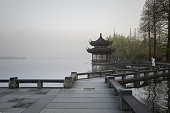 Hangzhou, China - March 30, 2019: Traditional Chinese ancient gazebo pavilion on the West Lake coast in Hangzhou city center. Few tourists visit west lake in early morning.