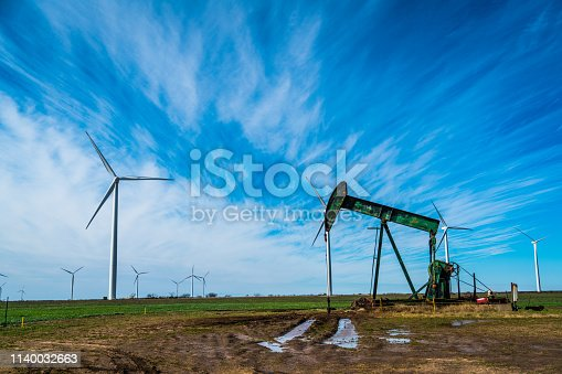 Oil platform pumping oil out of the ground near Lubbock , Texas in West Texas with wind turbines all around in a huge wind farm one of the worlds largest wind farms in sweet water , Texas