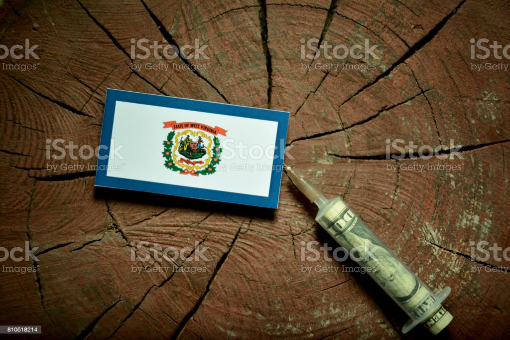 West Virginia flag on a stump with syringe injecting money in flag stock photo