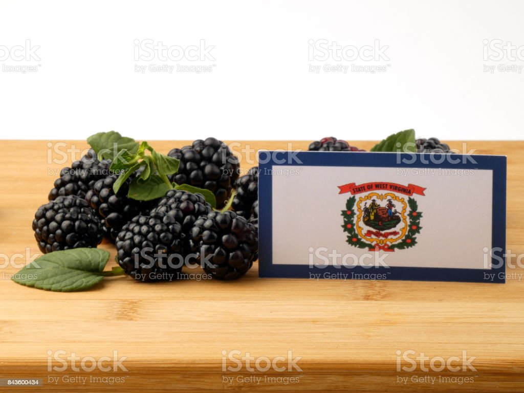 West Virginia flag on a wooden panel with blackberries isolated on a white background stock photo