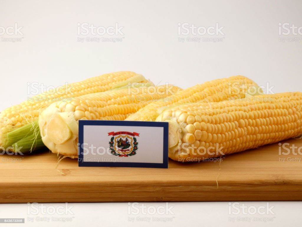 West Virginia flag on a wooden panel with corn isolated on a white background stock photo
