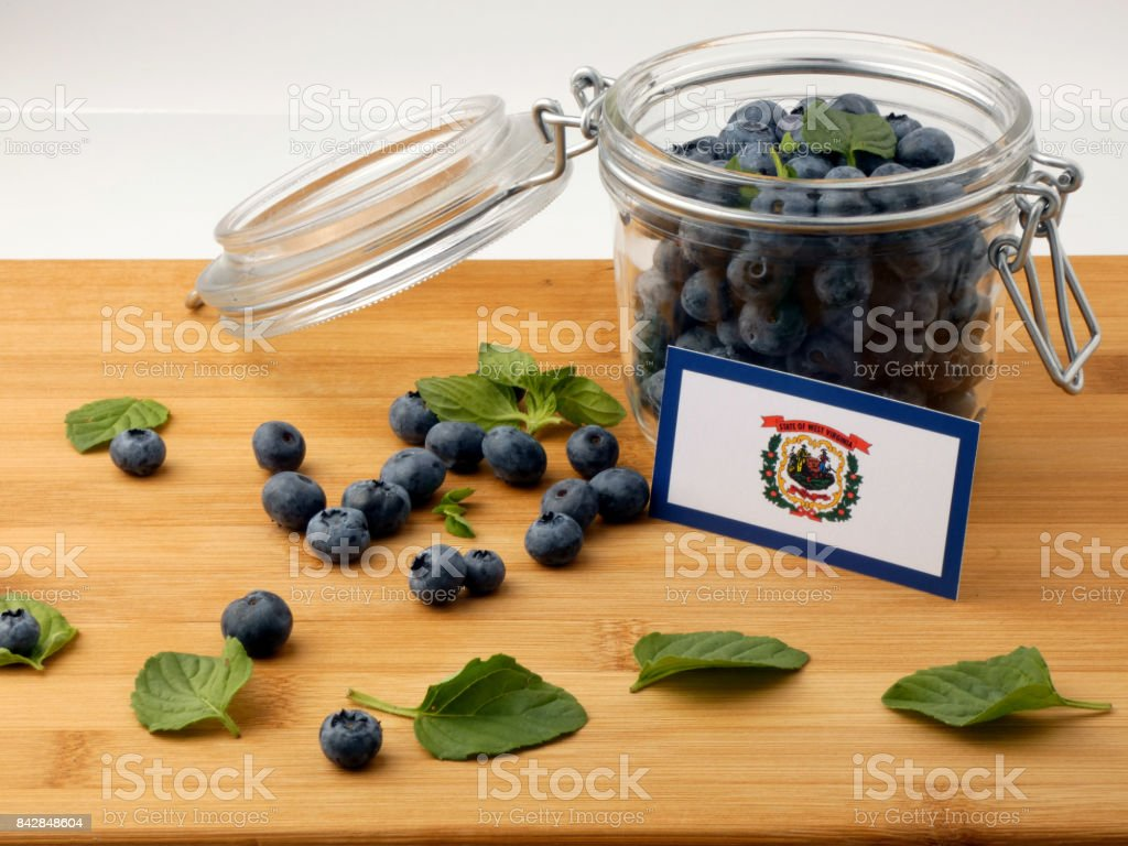 West Virginia flag on a wooden plank with blueberries isolated on white stock photo