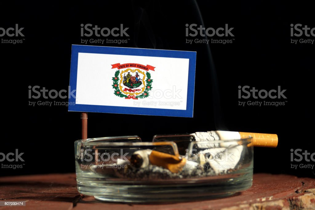 West Virginia flag with burning cigarette in ashtray isolated on black background stock photo