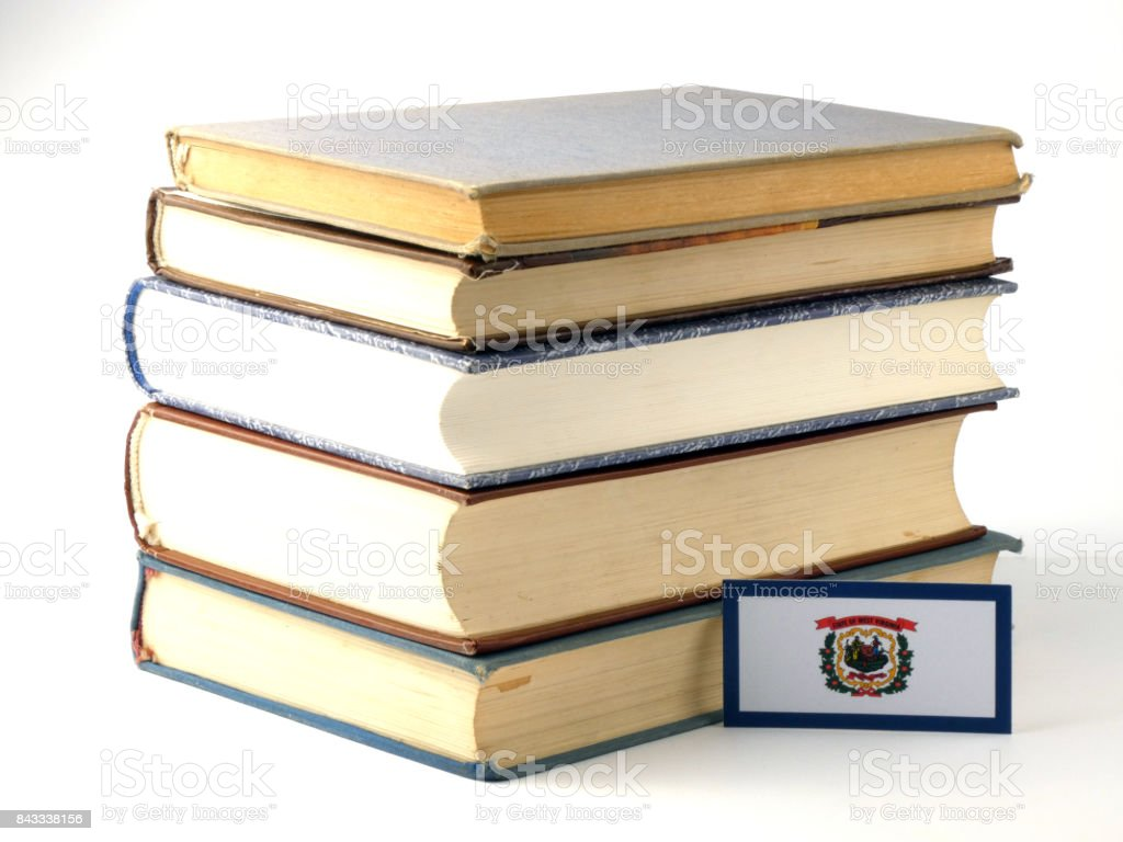 West Virginia flag with pile of books isolated on white background stock photo