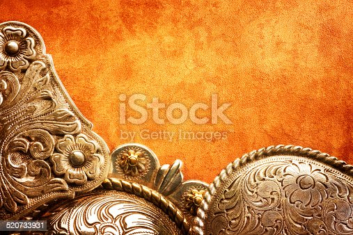 A western concho, and belt buckles, on a textured piece of leather.