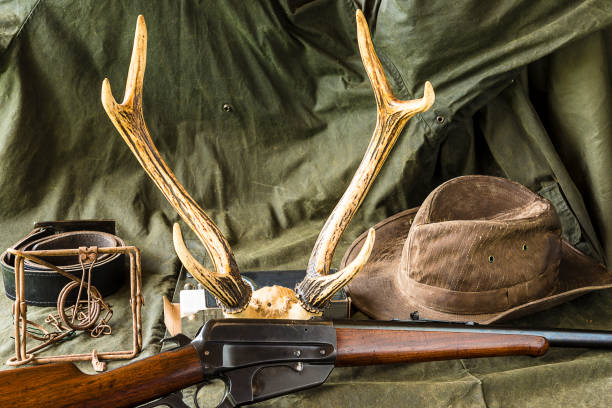 western concept hunting carbine, deer antlers, old trape and cowboy hat on hunting raincoat hunting blind stock pictures, royalty-free photos & images