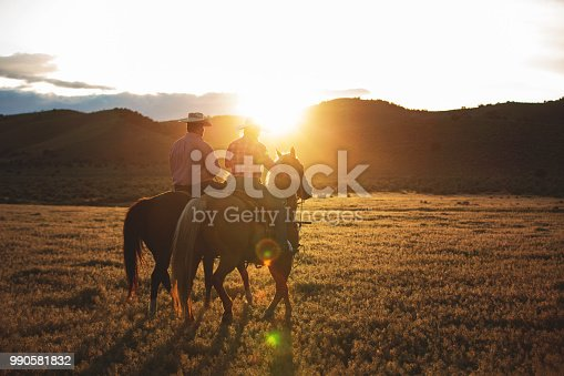 Cowboy and Cowgirl riding their horses into the sunset.