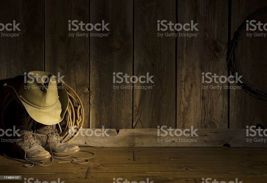 Western cowboy hat,packer's boots,rope on barn floor-spot lighting royalty-free stock photo
