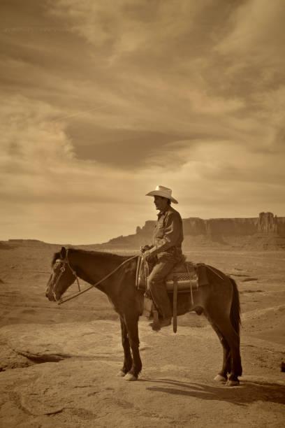western cowboy native american on horseback at monument valley tribal park - navajo stil stock-fotos und bilder