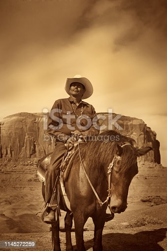 Portrait of a native American cowboy on horseback at the Monument Valley Tribal Park in Arizona, USA. A famous tourist destination in the southwest USA. The iconic western landscape is a backdrop for many western movies. The native American is a Navajo tribe native. Photographed on location.