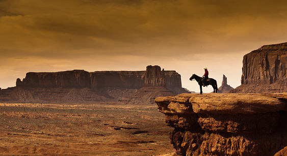 An Native American cowboy on horseback at the edge of a butte cliff at the Monument Valley Tribal Park in Arizona, USA. A famous tourist destination in the southwest USA. The iconic western landscape is a backdrop for many western movies. The native American is a Navajo tribe native. Photographed on location in desaturated sepia tone.