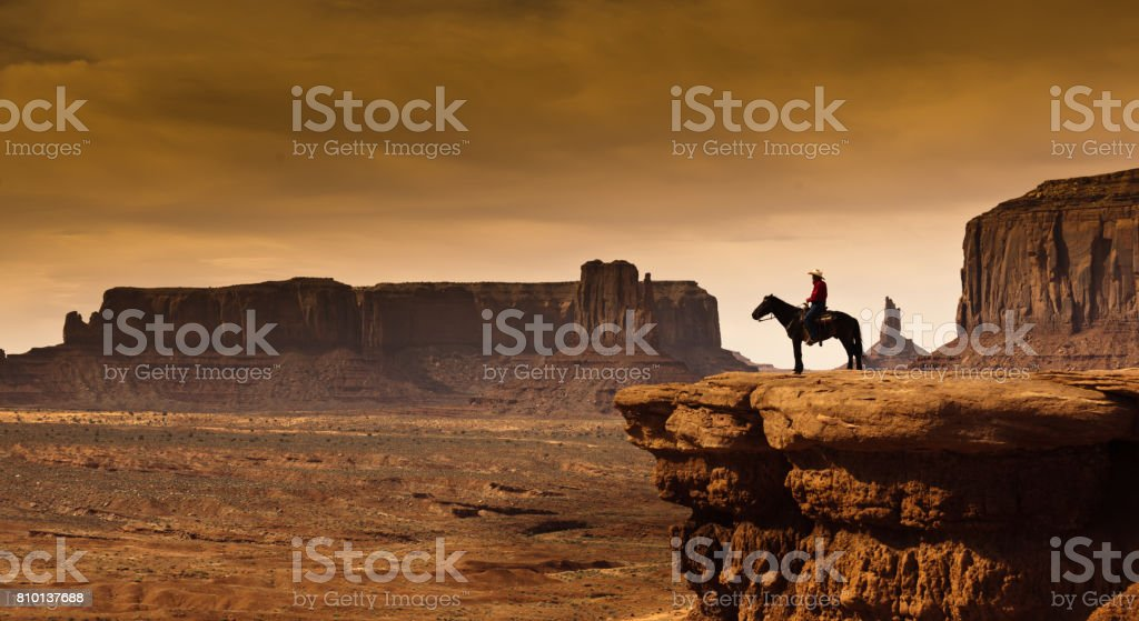 Western Cowboy Native American on Horseback at Monument Valley Tribal Park stock photo