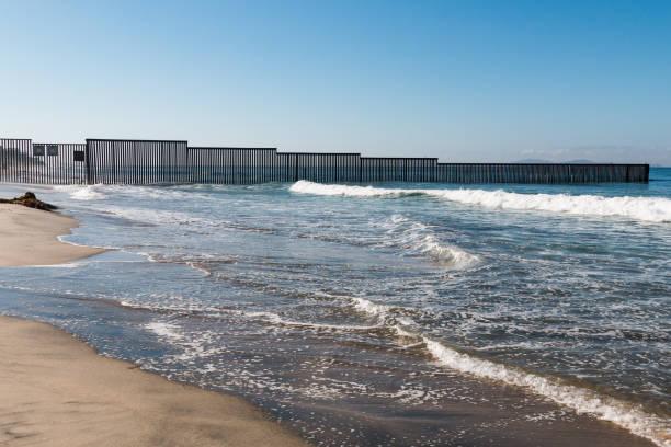 Western End of San Diego-Tijuana International Border Wall in Pacific Ocean stock photo