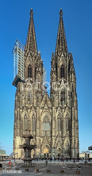 Western facade of the Cologne Cathedral in evening, Germany. Construction of the Cathedral began in 1248. Currently it is the tallest twin-spired church at 157 m (515 ft) tall.