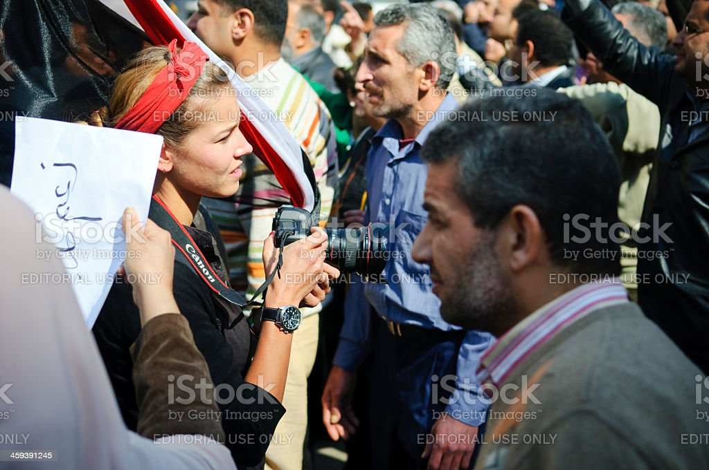 Western female photographer covering story in Middle East Cairo, Egypt - February 2, 2011: A young Western female photographer covers a pro-Mubarak rally in downtown Cairo. She is using a Canon DSLR. Adult Stock Photo