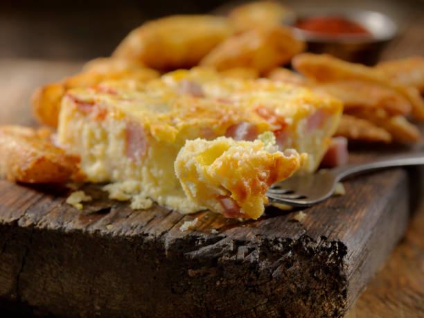 westliche frittata mit heimfries, schinken, pfeffer und cheddar-käse - kartoffel frittata stock-fotos und bilder