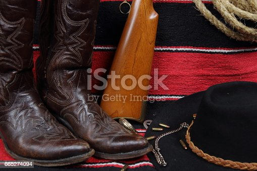 Western Gear - several items related to the old west and cowboys sit on a saddle blanket with geometric designs.  Objects include cowboy boots, cowboy hat, sheriff badge, gold pocket watch, coil of rope or a lasso, bullets, and a gold chain
