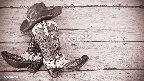 cowboy boots and hat on a wood background with vintage tinted effect and writing space