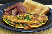 Macro view of a Western or Denver omelet with sides of bacon and toast.  Selective focus on omelet front.