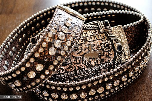 A very close up photo of a western bling rhinestone belt with trophy belt buckle on  wood table.