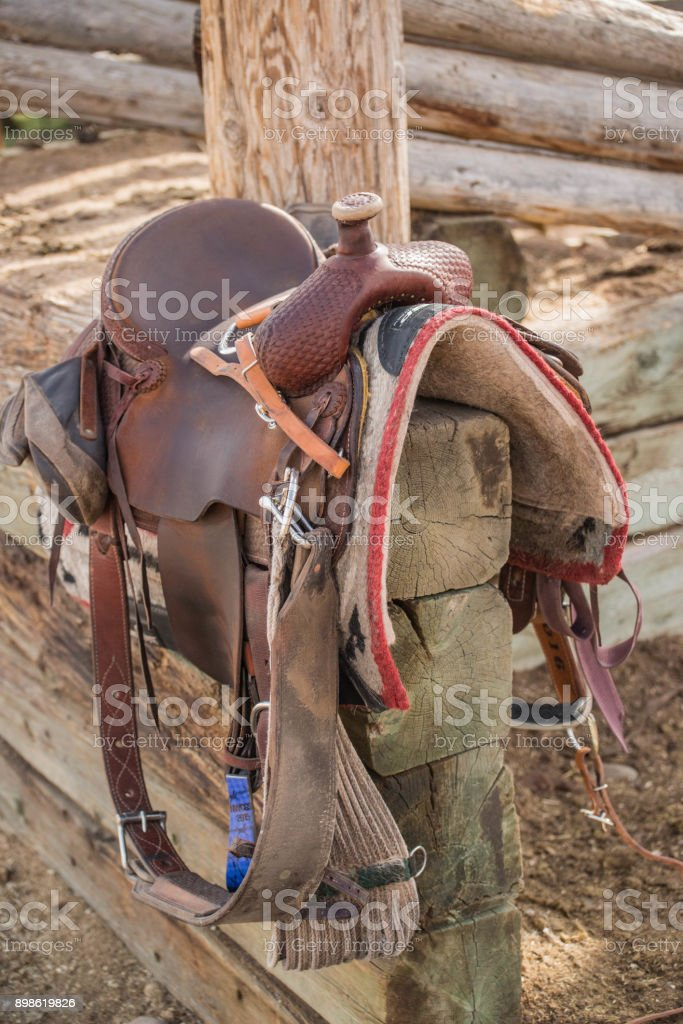 Western riding saddle and horse blanket on wooden corral post stock photo