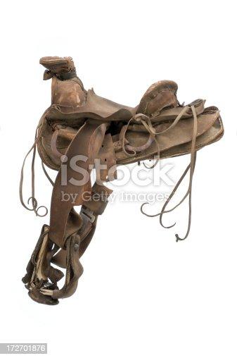old well worn western saddle isolated on 255 white background.
