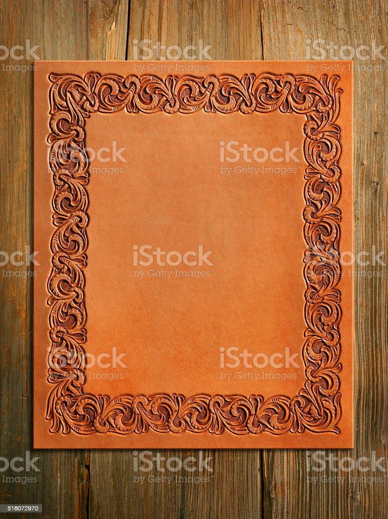 Western Style Stamped Leather Sitting On Old Wood stock photo