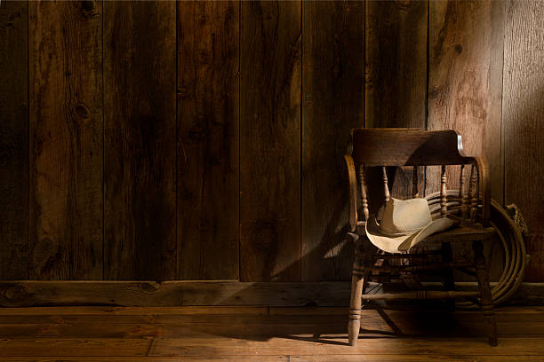 Western theme with rustic barnwood and saloon chair This image has subdued rustic barnwood with a vintage saloon chair, cowboy hat and lasso. A shaft of soft sun ray comes in from the right to highlight the chair and hat. Room for overprint saloon stock pictures, royalty-free photos & images
