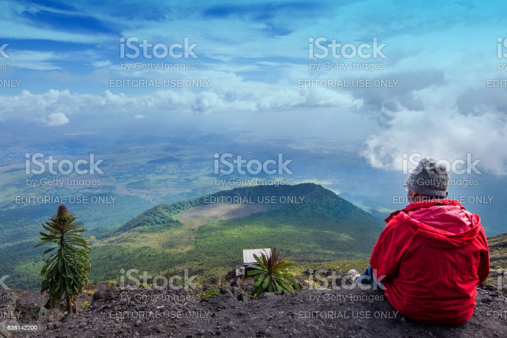 Western tourist is sitting at the crater of Nyiragongo Volcano stock photo