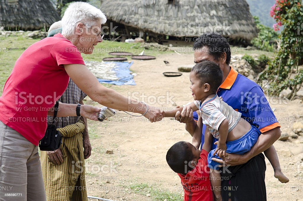 Western tourist shaking hands with Indonesian child royalty-free stock photo