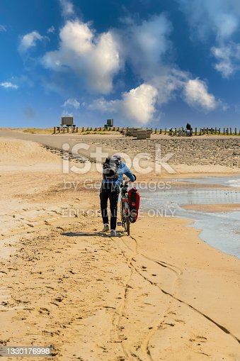 istock Westkapelle, Netherlands - 26 April 2021: Cyclist pushing a trekking bike with baggage on a sandy beach. 1330176998