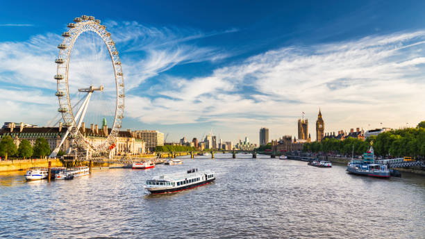 Westminster Parliament, Big Ben and the Thames with blue sky LONDON, JULY 2017 - View of Westminster Parliament, Big Ben and London Eye with Thames and tourist ship in foreground on a sunny summer afternoon ferris wheel stock pictures, royalty-free photos & images