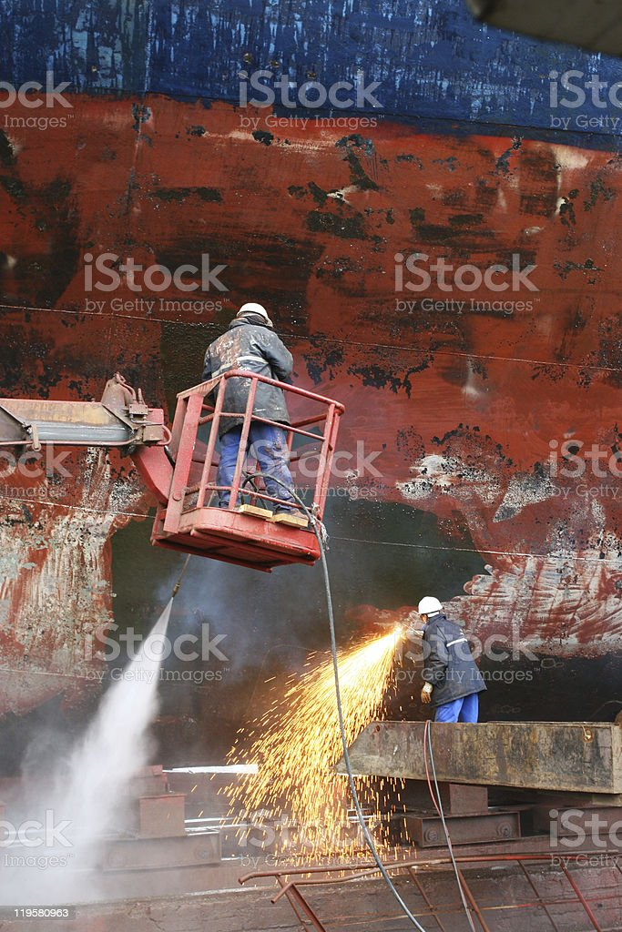 Wet and dry scraping process made to a ship surface stock photo