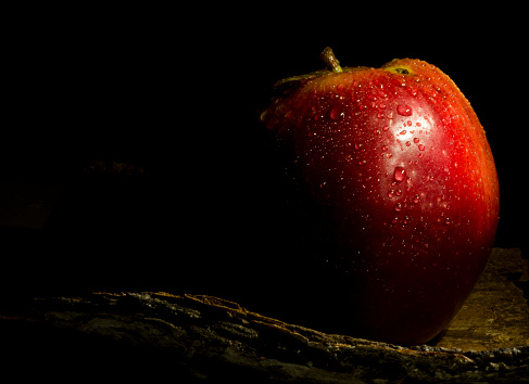 red wet apple in light painting with dark background