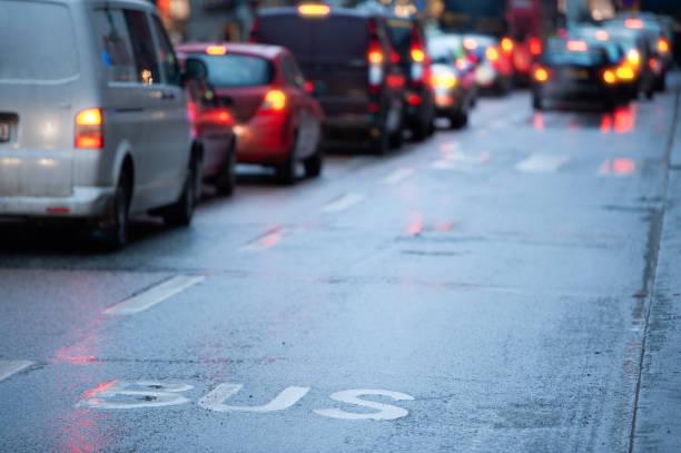 Wet bus lane asphalt street car queue stock photo