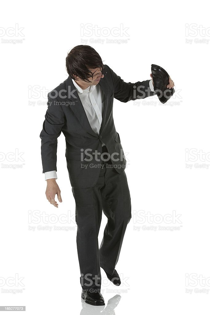 Wet businessman holding his shoe stock photo
