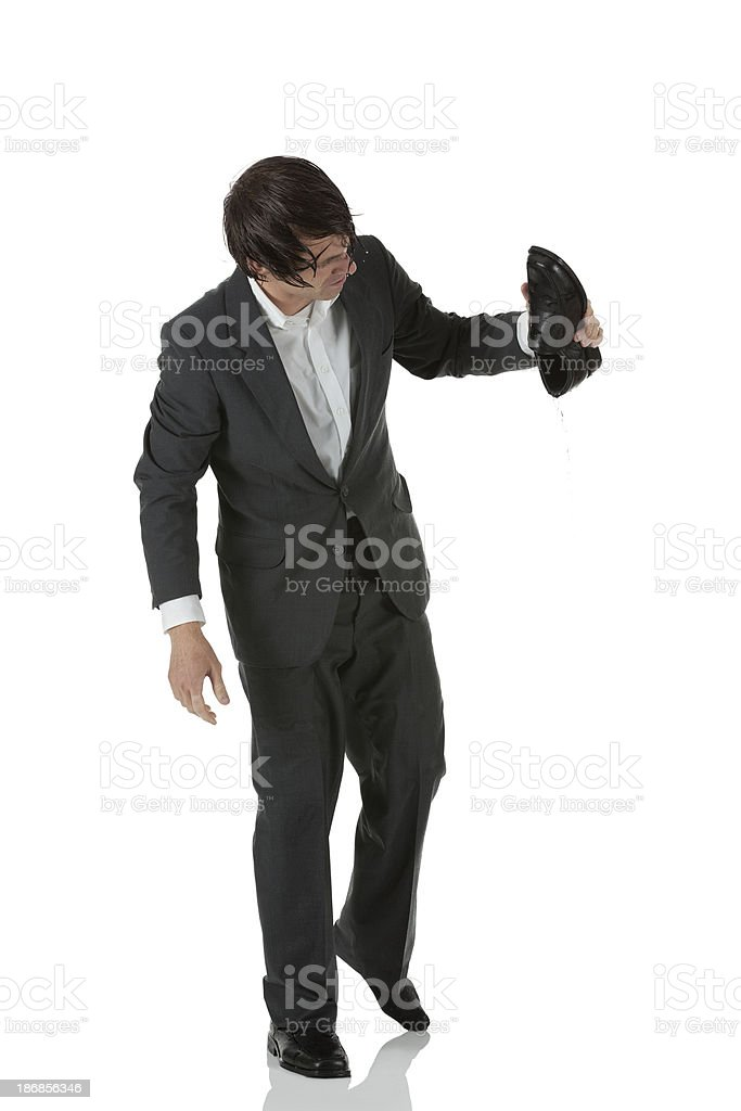 Wet businessman holding his shoe royalty-free stock photo