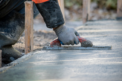 A construction worker is Smoothing wet cement
