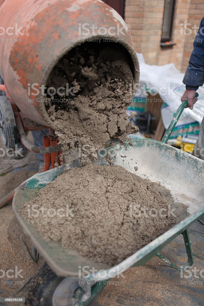 Wet cement pouring from a cement mixer into a wheelbarrow royalty-free stock photo