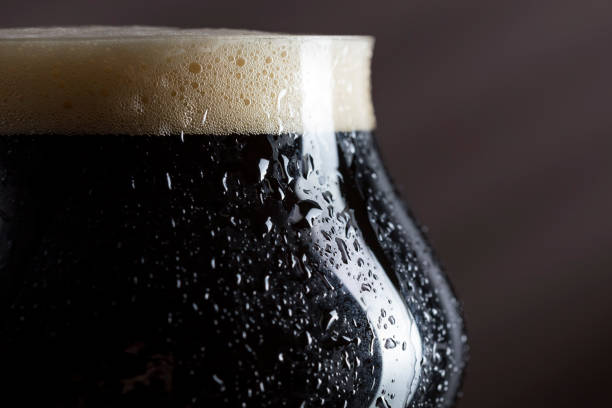 Wet dark beer glass Close up of a wet glass of cold dark beer with foam. Selective focus bitter ale stock pictures, royalty-free photos & images