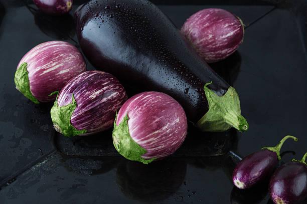 wet eggplant varieties on rustic frying pan closeup - black beauty photos et images de collection