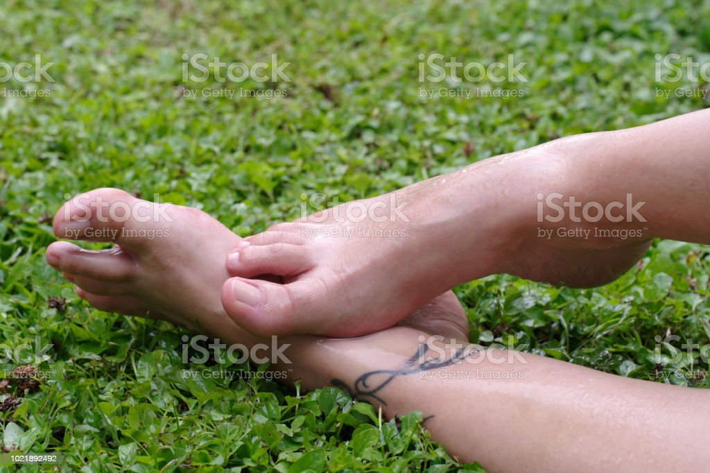 Wet female feet on grass with natural nails - Foto stock royalty-free di Adulto