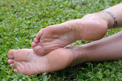 Wet Female Feet Soles On Grass — стоковые фотографии и другие картинки Взрослый