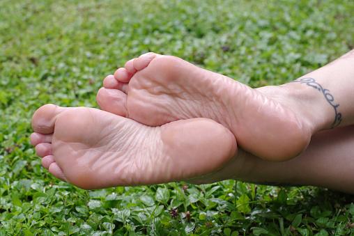 Wet Female Feet Soles On Grass - Fotografie stock e altre immagini di Adulto