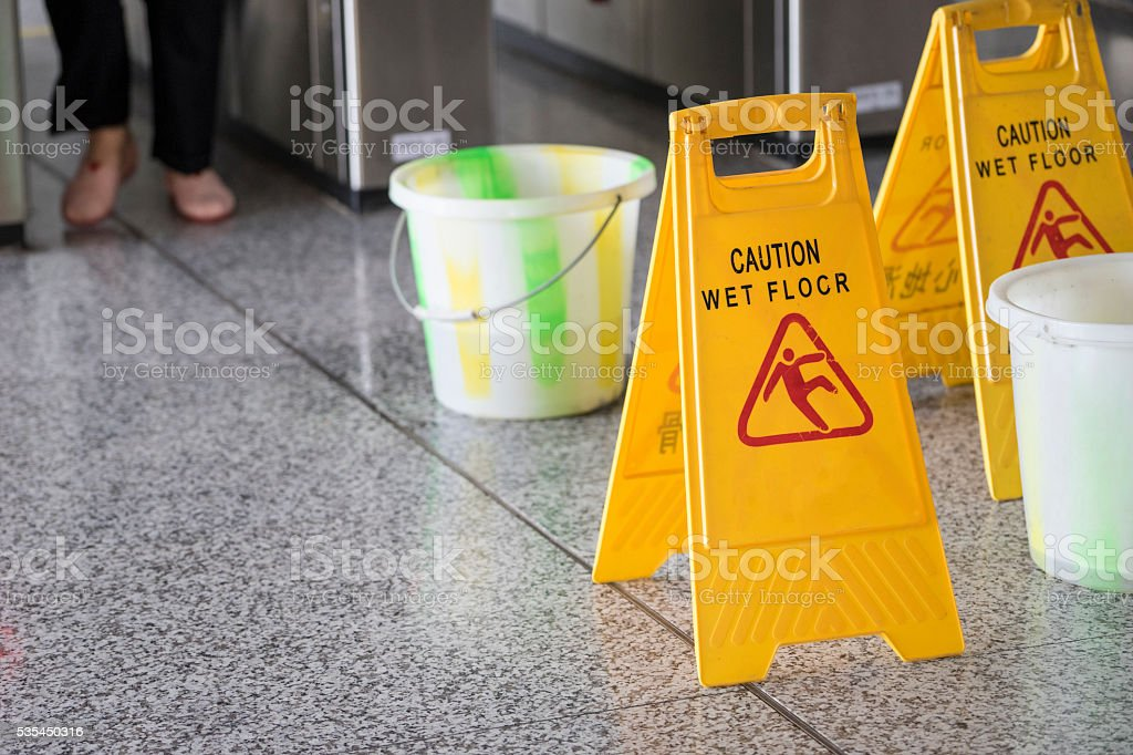 Wet floor caution sign on subway station floor.
