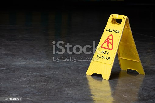 wet floor sign on cement ground. yellow plastic warning sign.
