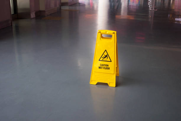 Wet Floor Sign Elevated view of yellow warning sign on floor. stealth stock pictures, royalty-free photos & images