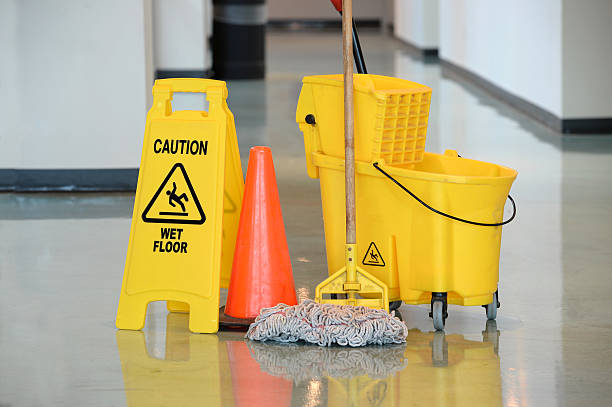 Wet Floor Sign With Mop Caution sign with mop and bucket on office floor cleaning equipment stock pictures, royalty-free photos & images