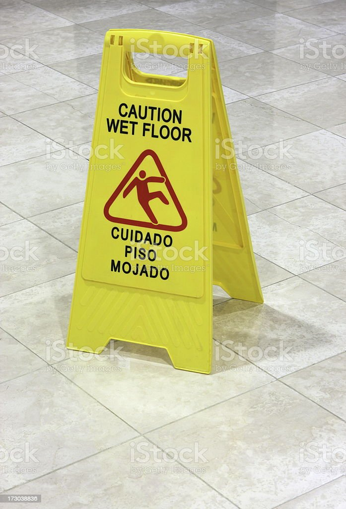 Bi-lingual wet floor warning sign in English and Spanish cautions...