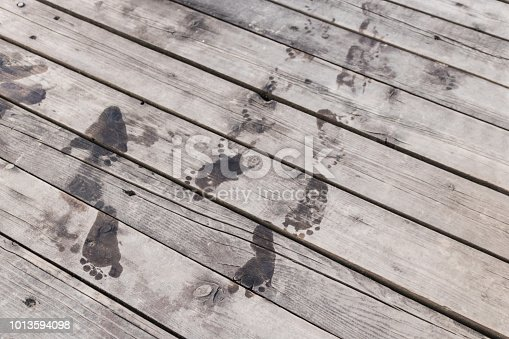 1088451256 istock photo Wet footprints on a pier. 1013594098